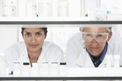 Scientists Looking Through Shelves. Two multiethnic scientists looking through shelves in laboratory Stock Photos