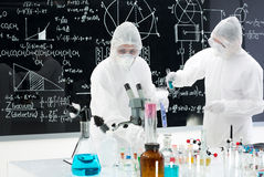 Scientists manipulating lab tools. General-view of two people studying and testing substances in a lab with lab tools and colorful liquids and a blackboard with Royalty Free Stock Photo