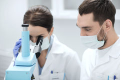 Scientists in masks looking to microscope at lab Stock Images