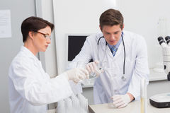 Scientists pouring chemical fluid in funnel Stock Photo