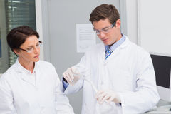 Scientists pouring chemical fluid in funnel. In laboratory Stock Photos