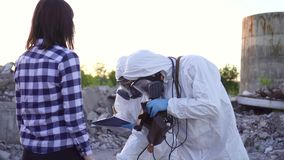 Scientists in protective suits and masks and personal ionizing radiation dosimeter ,measure radiation and affected