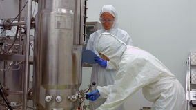 Scientists in protective suits working together. In high quality 4k format stock video
