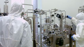 Scientists in protective suits working on vat stock video