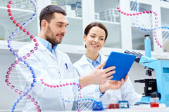 Scientists with tablet pc and microscope in lab Stock Images