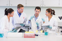 Scientists with tablet PC working on experiment at lab Royalty Free Stock Photo