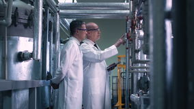 Scientists talking and touching valve. Two scientists with a tablet talking and touching valve while inspecting the factory stock video