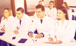 Scientists at training courses. Group of positive scientists in white overalls at advanced training courses. Focus on man Stock Images