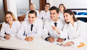 Scientists at training courses. Group of smiling specialists in white uniform at advanced training courses Stock Photo