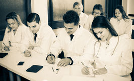 Scientists at training courses. Group of smiling scientists in white uniform at advanced training courses. Focus on man Stock Photography