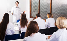 Scientists at training courses. Group of specialists in white overalls at advanced training courses Stock Image