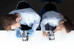 Scientists in uniforms working with microscopes in laboratory. Top view of scientists in uniforms working with microscopes in laboratory Royalty Free Stock Image