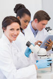 Scientists using microscope and tablet pc. In the laboratory Royalty Free Stock Photography