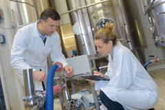 Scientists using tablet to control vats in lab. Scientists using tablet to control vats in the lab Stock Photos