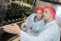 Scientists wearing lab coat and hair net in factory. Scientists wearing lab coat and hair net in the factory Stock Image