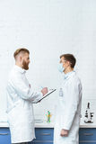 Scientists in white coats discussing experiment results in lab Royalty Free Stock Photo