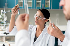 Scientists in white coats examining test tubes with reagents in chemical lab. Young scientists in white coats examining test tubes with reagents in chemical lab stock photo