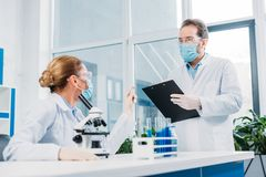 Scientists in white coats and goggles working with reagents and microscope. In laboratory royalty free stock photo