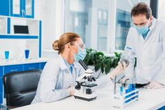Scientists in white coats and goggles working with reagents and microscope. In laboratory stock photo
