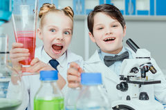 Scientists in white coats making experiment with reagents and microscope in science laboratory. Little scientists in white coats making experiment with reagents stock image