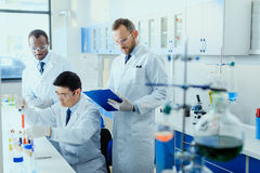Scientists in white coats working together in chemical laboratory. Professional scientists in white coats working together in chemical laboratory Stock Images