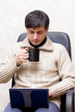 Scientists at work. A male scientific researcher using his laptop and drinking coffee Royalty Free Stock Photography