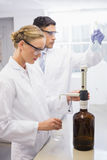 Scientists working attentively with beaker Stock Image