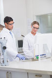 Scientists working on computer together Stock Photos