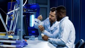 Scientists working on 3-D printing in medicine purposes. Side view of multiethnic researchers discussing possibilities of 3-D printing for prosthetic and medical Royalty Free Stock Photo