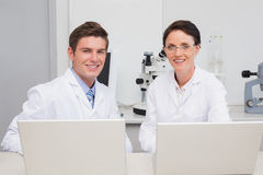 Scientists working with laptop and smiling at camera. In laboratory Stock Photos
