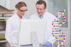 Scientists working on laptop together Stock Photos