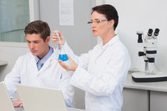 Scientists working with laptop and using a beaker Stock Photography