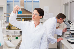 Scientists working with microscope and beaker. In laboratory Stock Images