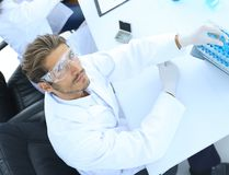 Scientists working with a microscope and make notes in the workplace Royalty Free Stock Photography
