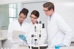 Scientists working with microscope and taking notes. In laboratory Stock Photography