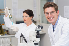Scientists working with microscope and test tube Royalty Free Stock Image
