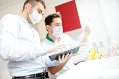 Scientists working on tablet in laboratory with experiments and tools Royalty Free Stock Photography