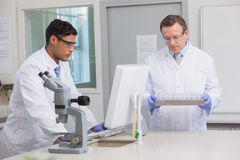 Scientists working together on tubes and computer Royalty Free Stock Photography