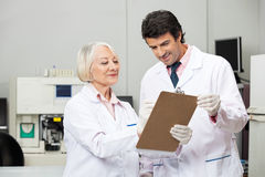 Scientists Writing On Clipboard In Laboratory. Male and female scientists writing on clipboard in medical laboratory Royalty Free Stock Image