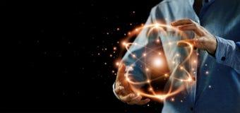 Scienza astratta, mani che tengono particella atomica, energia nucleare immagini stock libere da diritti