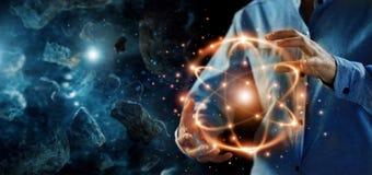 Scienza astratta, mani che tengono particella atomica, energia nucleare immagine stock