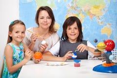 Scienza ed arte - bambini che fanno il modello di scala del sistema solare Fotografia Stock