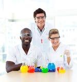 Scienziati che esaminano sorridere dei prova-tubi Immagini Stock