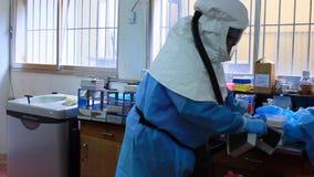 Scienziati che manipolano il materiale contaminato agente patogeno del microbo dallo scoppio di infezione video d archivio