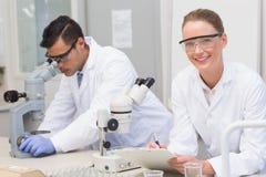 Scienziati che per mezzo del microscopio Fotografia Stock Libera da Diritti