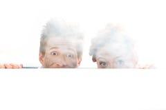 Scienziati colpiti che guardano fuori dietro la tavola dopo l'esperimento su bianco Immagine Stock Libera da Diritti
