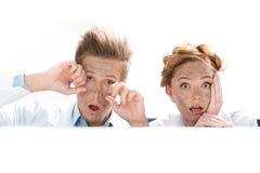 Scienziati colpiti che guardano fuori dietro la tavola dopo l'esperimento su bianco Fotografia Stock