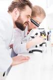Scienziati dello studente e dell'insegnante che lavorano con il microscopio Fotografia Stock