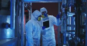 Scienziati nei vestiti del hazmat che conducono il lavoro di manutenzione archivi video