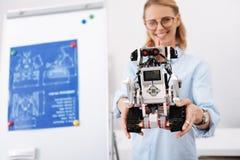 Scienziato amichevole che dimostra il robot automatico di nuovo auto all'interno Fotografia Stock Libera da Diritti